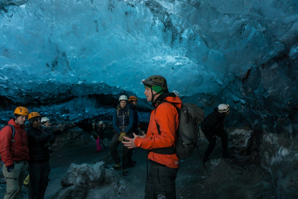 Ice cave tour guide inside an ice cave in Iceland. The Ultimate Guide to Ice Caves in Iceland: Everything you ever needed to know about visiting ice caves in Iceland. Find out how to go INSIDE the Crystal Cave glacier ice cave to see the blue ice.