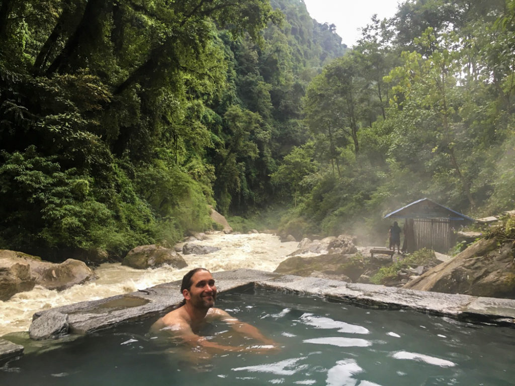 A trekker relaxes in the hot spring at Jhinu Danda on the Annapurna Base Camp trek. What to pack for the Annapurna Base Camp Trek in Nepal.