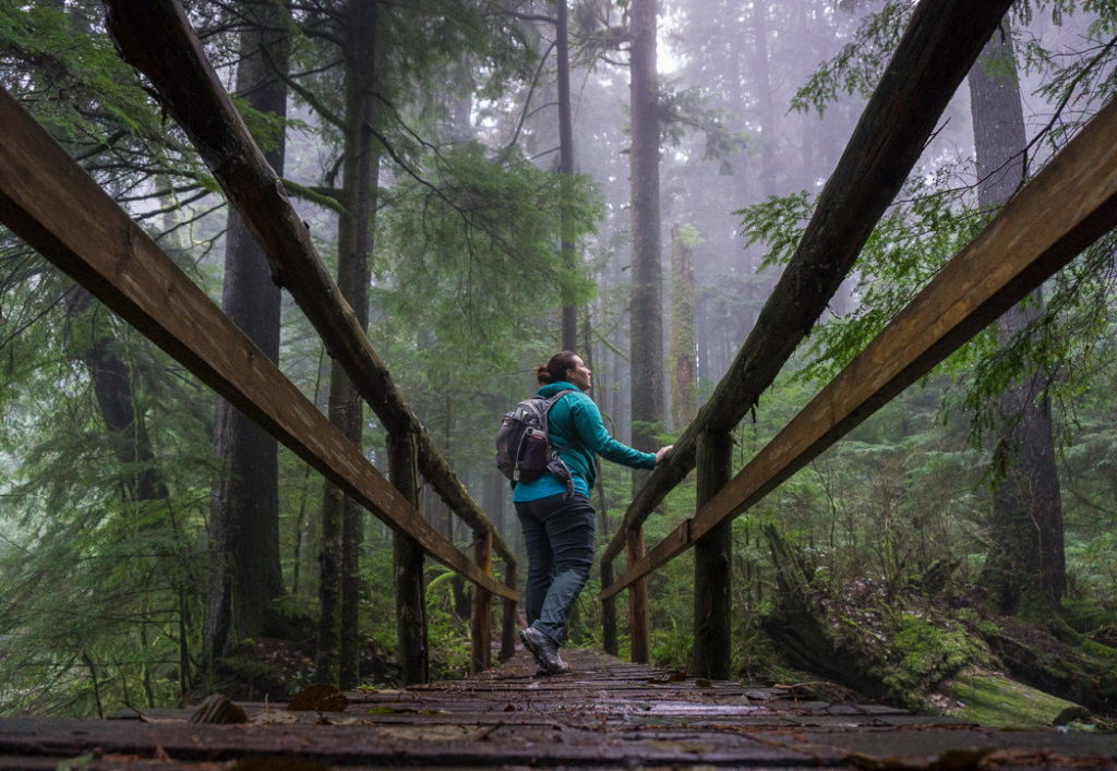A hiker in the fog. Hiking in bad weather is one way to avoid crowded trails.