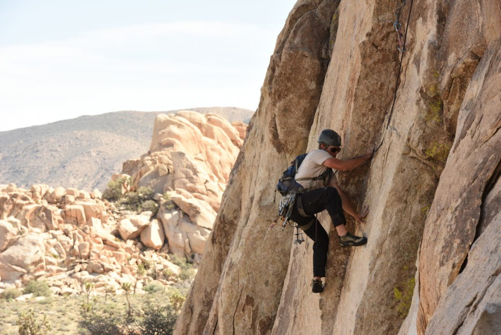 A rock climber in Joshua Tree National Park, one of 15 awesome things to do in Joshua Tree. Add rock climbing (or just watching the rock climbers) to your Joshua Tree bucketlist.
