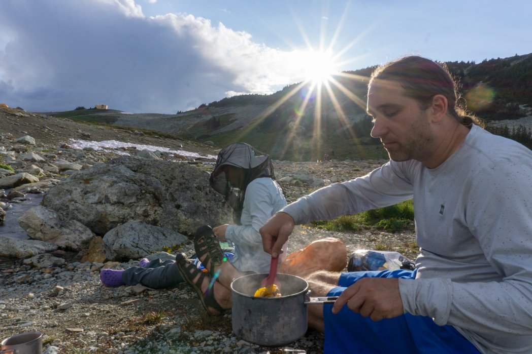 Person cooking dinner on a camp stove on a backpacking trip. How to choose backpacking meals.