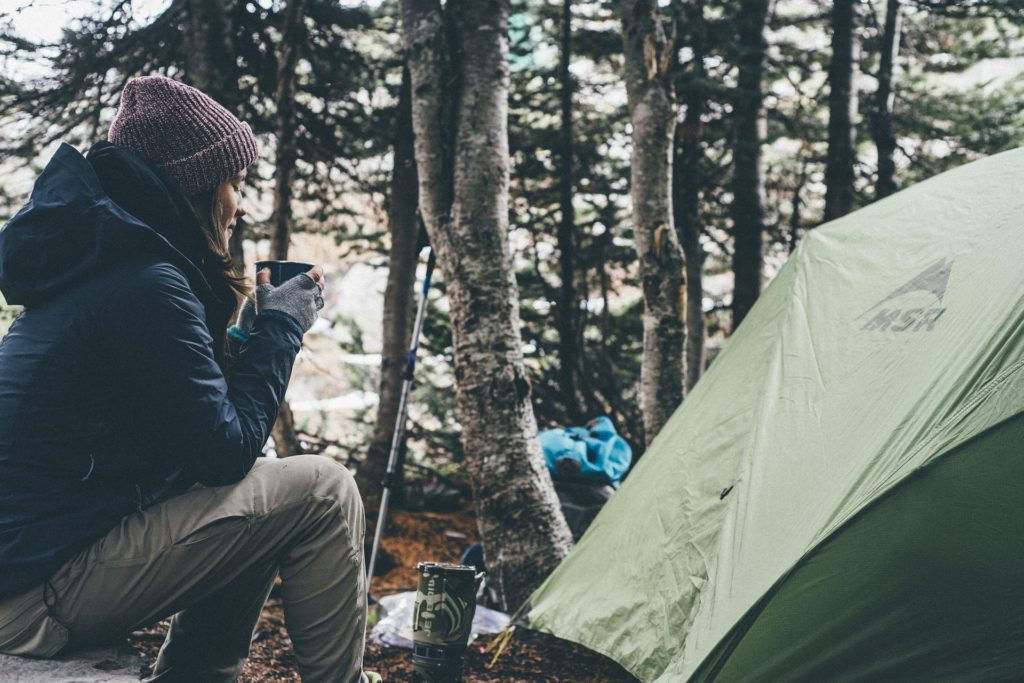 Person cooking at a backcountry campsite. How to choose backpacking meals.