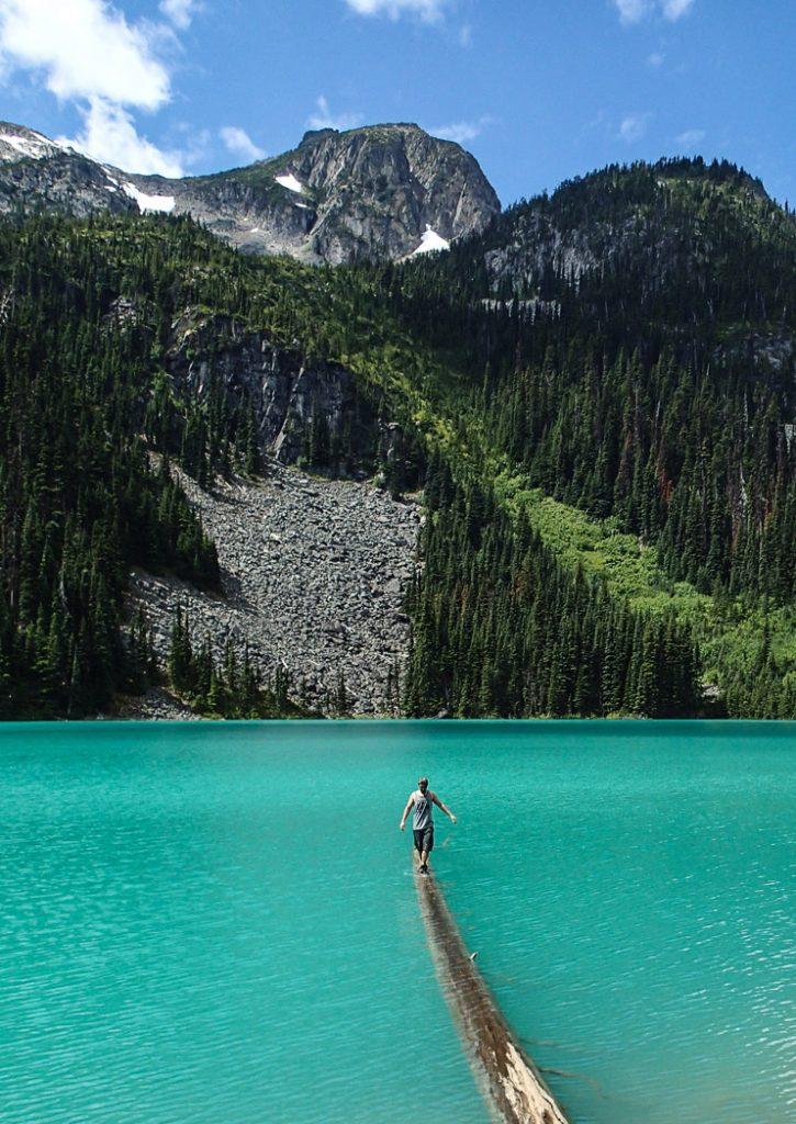 A hiker balances on a log at Joffre Lakes near Vancouver
