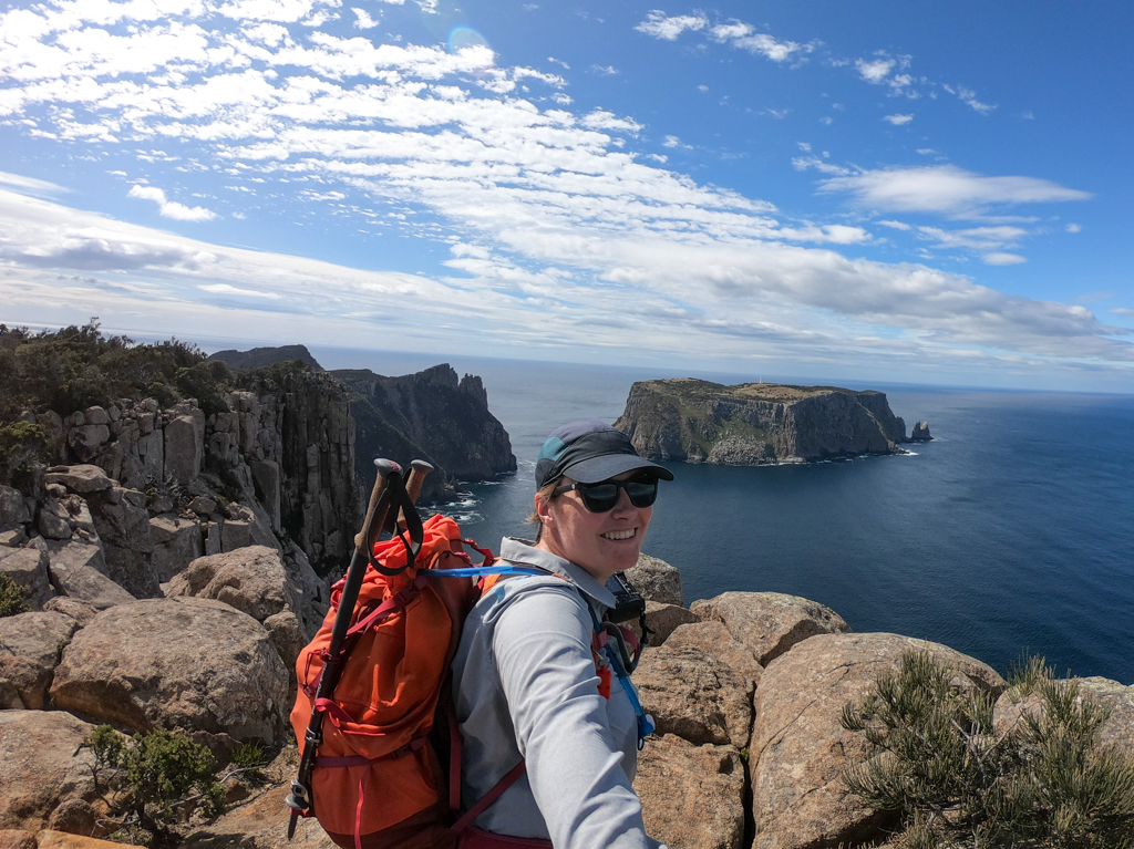 A hiker takes a selfie in front of the view of Tasman Island on the Cape Pillar Track in Tasmania
