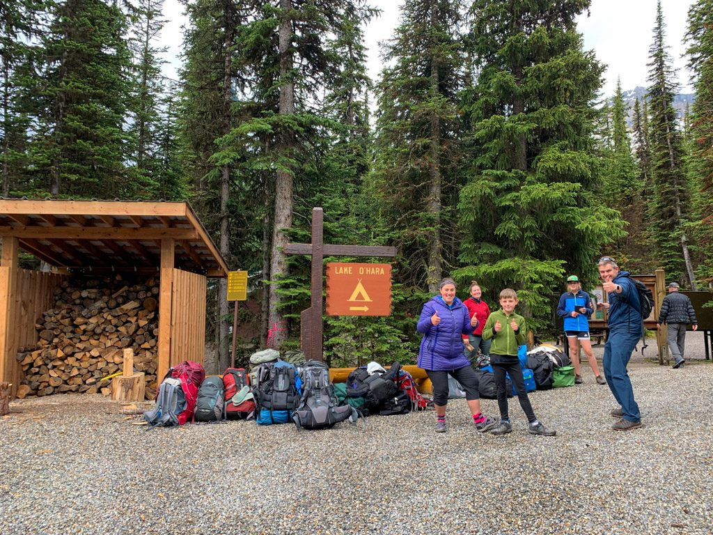 People and luggage waiting for the bus at the Lake O'Hara campground