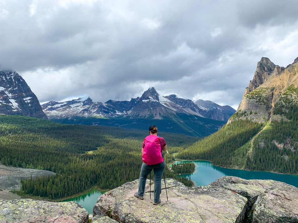 A hiker wearing a backpack with a rain cover on it at Opabin Prospect near Lake O'Hara in Yoho National Park. A raincover is an essential item on any Lake O'Hara packing list.