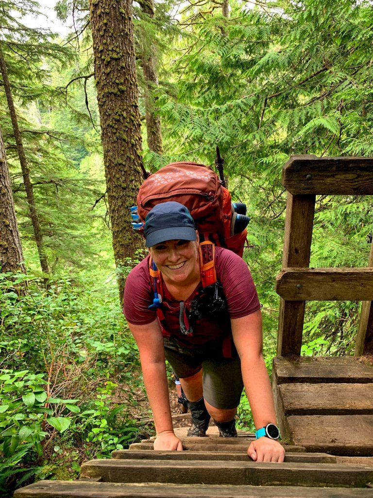 A hiker climbs a ladder on the West Coast Trail