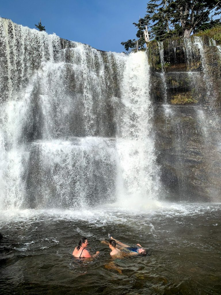 Hikers swimming at Tsusiat Falls on the West Coast Trail
