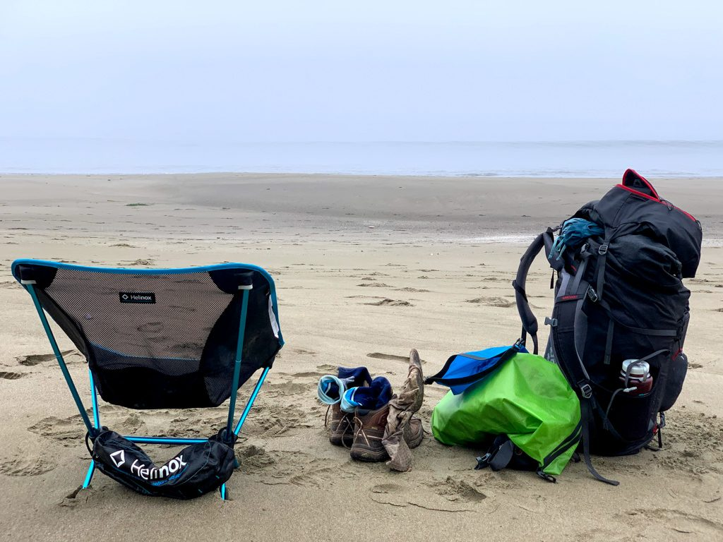 A backpacking chair on the beach next to a backpacking pack