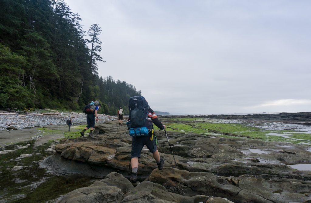Hikers walking on the rocky coastal shelf near Michigan Creek on the West Coast Trail