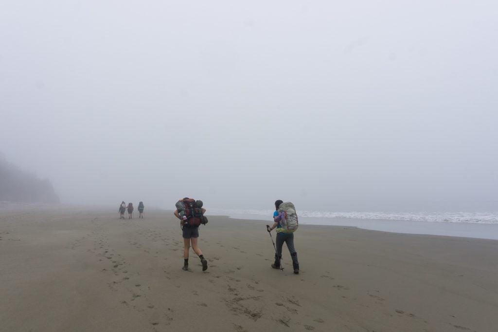 Hikers walk through fog on the beach on the West Coast Trail