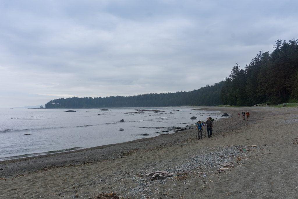 Hikers walk through soft sand near Carmanah River on the West Coast Trail