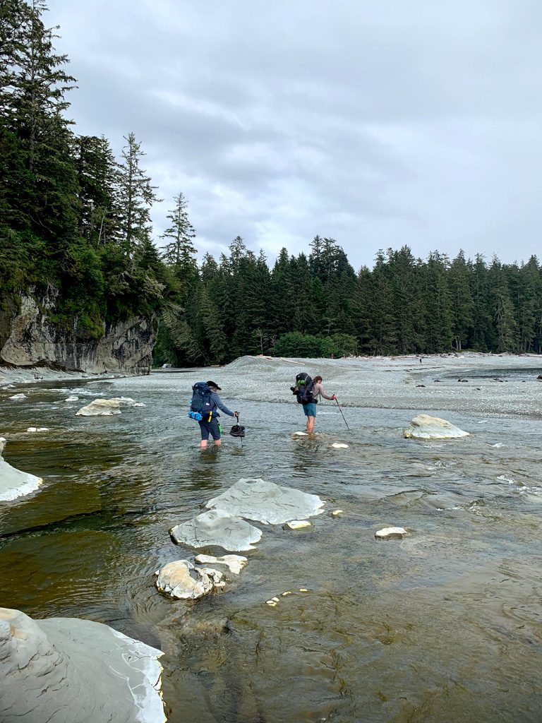 Hikers wade across the mouth of Walbran Creek on the West Coast Trail