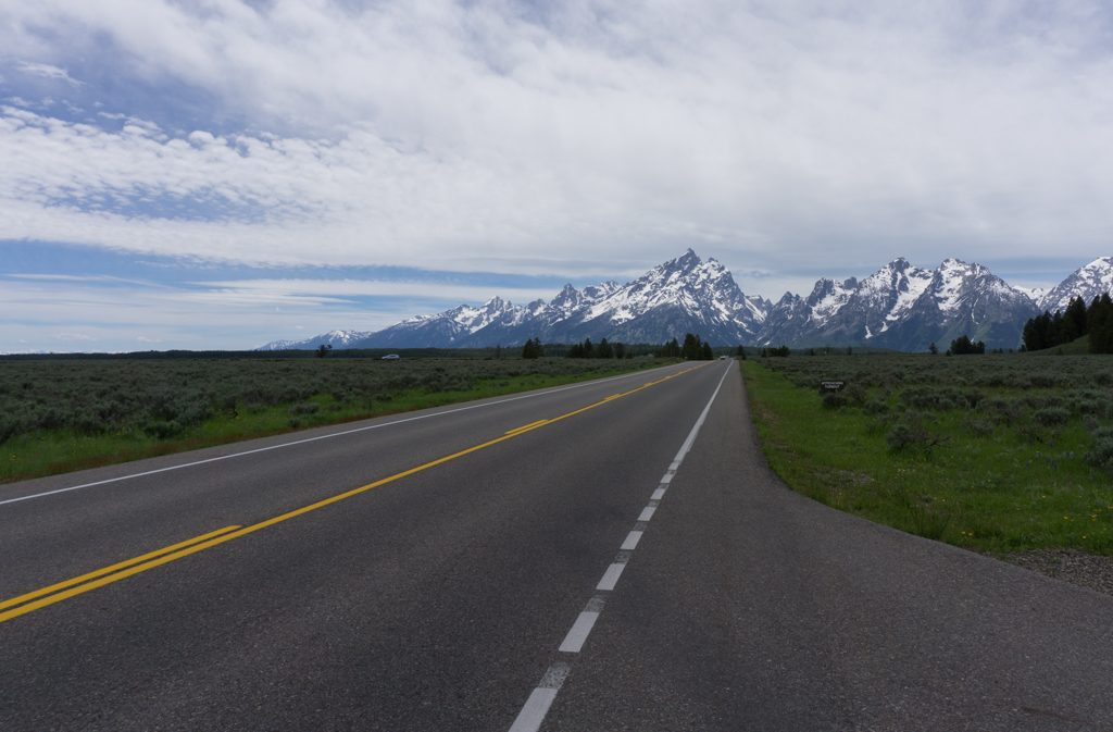 A road in Grand Teton National Park with mountains in the background