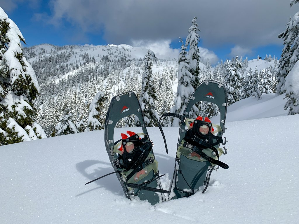 A pair of MSR snowshoes propped up in the snow in front of a mountain