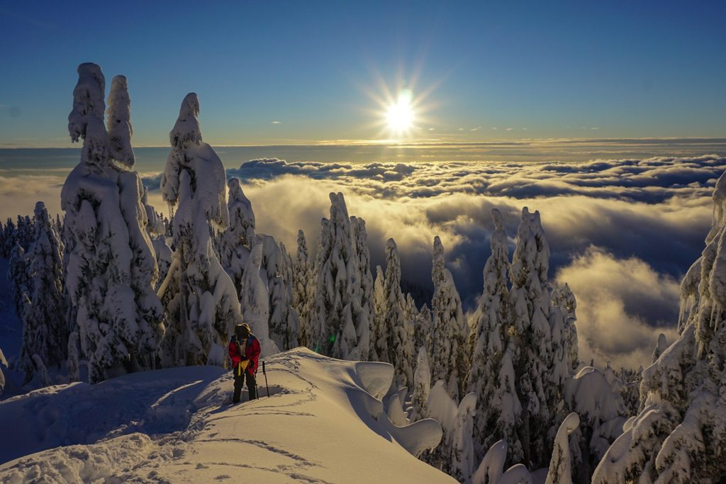 A snowshoer stands on top of a peak above the clouds