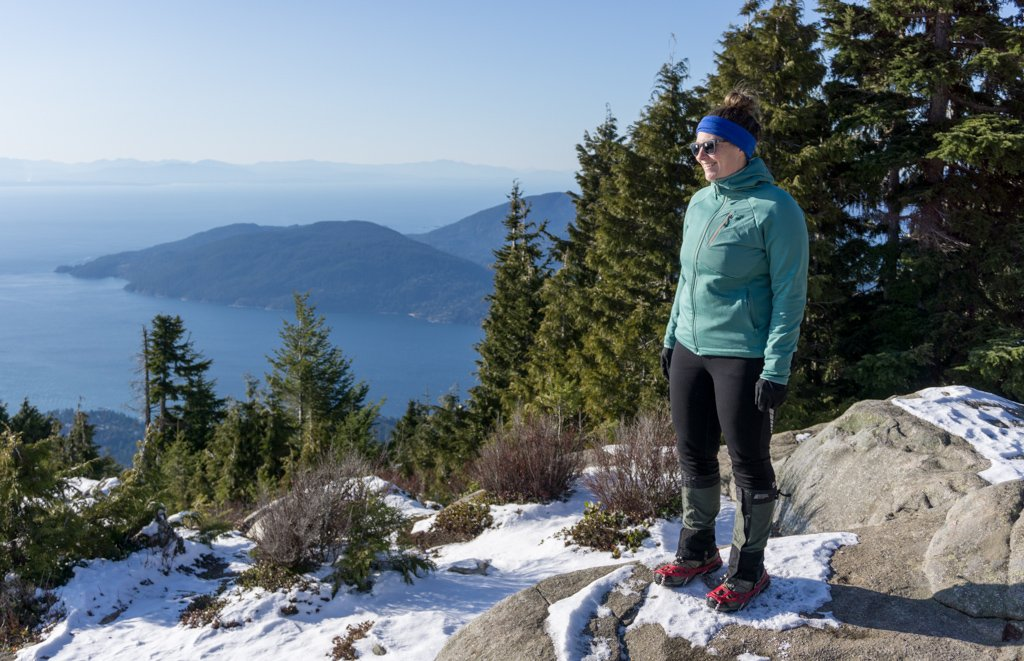 A hiker stands on top of a rocky bluff in the snow wearing microspikes