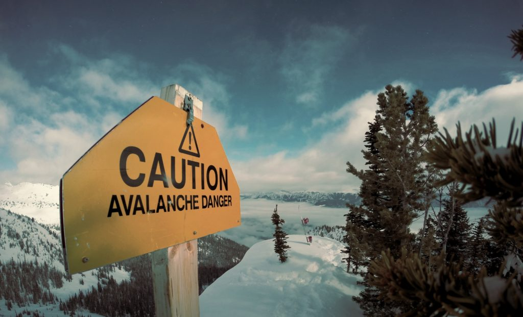 A sign warns of avalanche danger on a snowy mountain