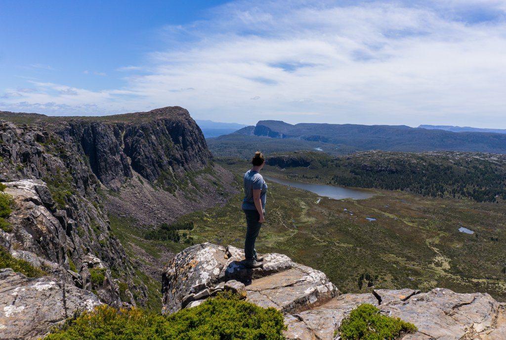 A hiker stands at the peak of Solomon's Throne in Tasmania's highlands