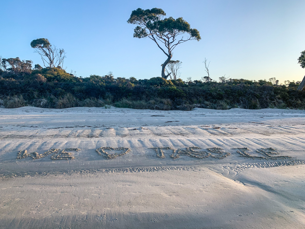 """Letters in the sand spell out """"We love Tassie"""""""
