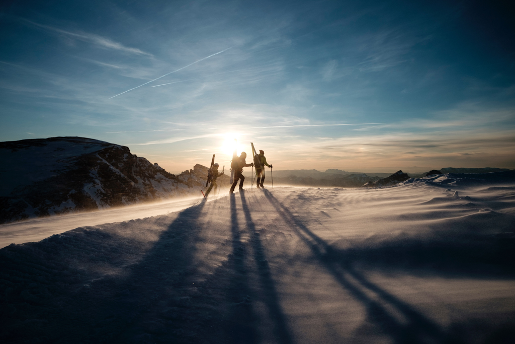 Three people ski touring as the sun sets