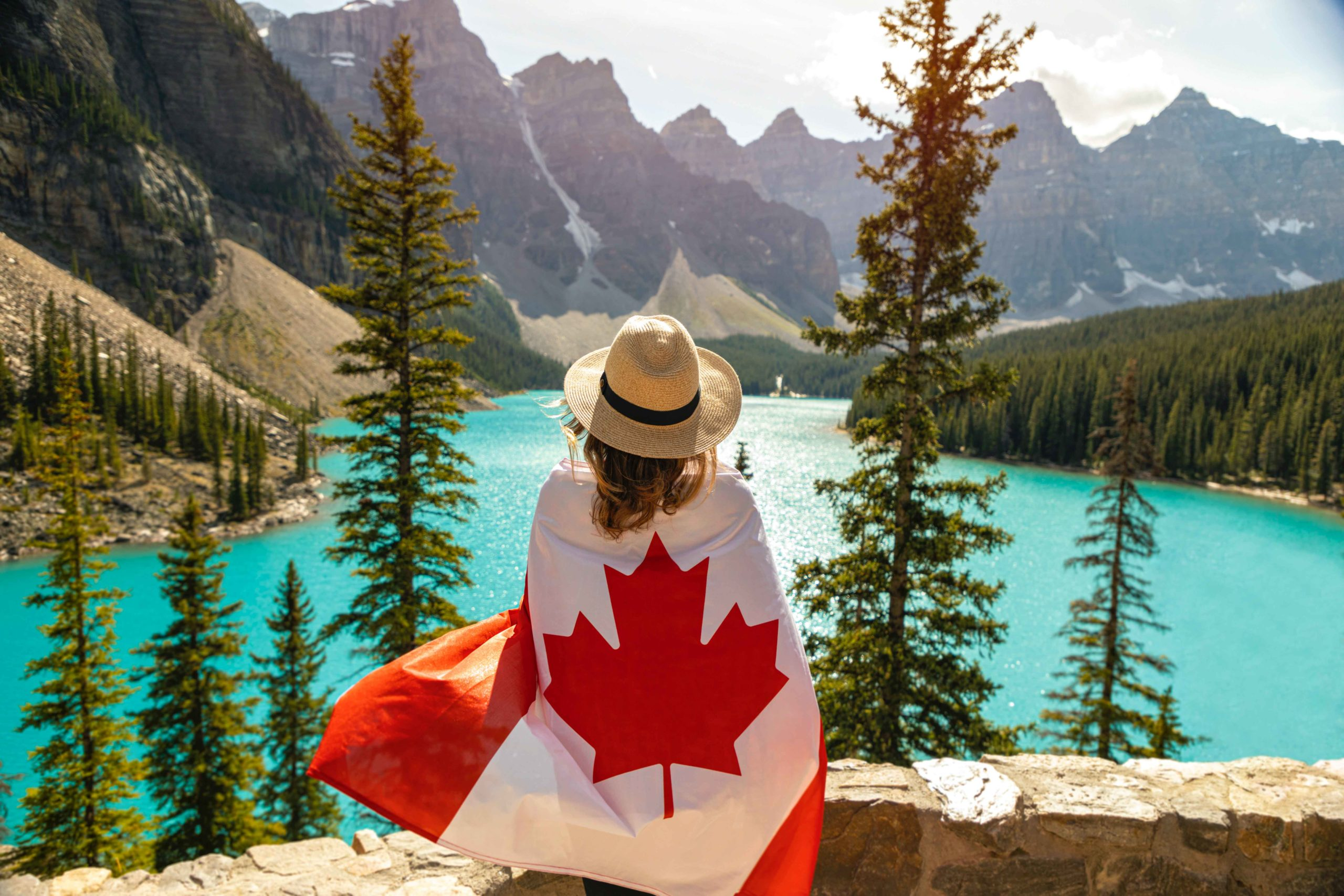 Woman Draped in the Canadian Flag near lake and mountains. The best Canadian adventure books