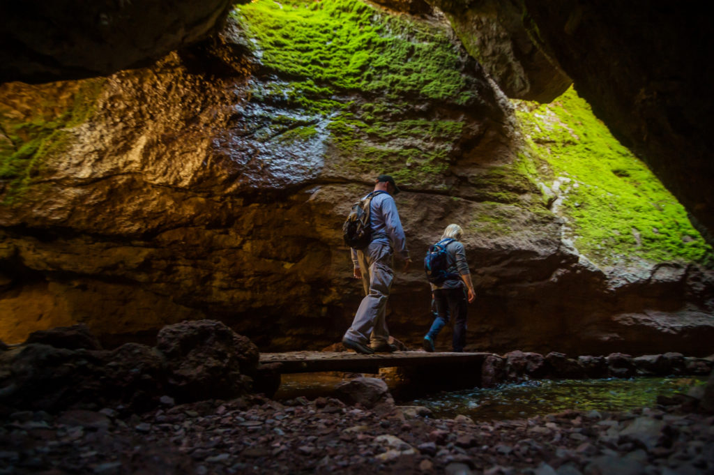 Two hikers walk along a boardwalk into Bear Gulch Cave in Pinnacles National Park in California - it's an under-the-radar US National Park