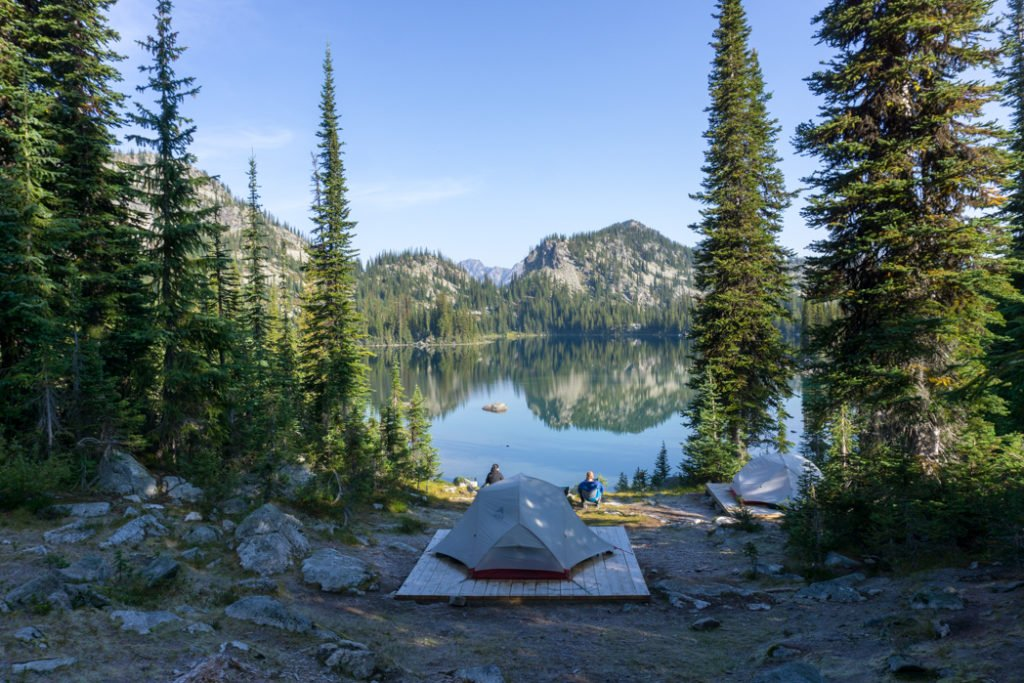 A backpacking tent in front of a still lake at Kokanee Glacier Provincial Park in British Columbia. Learn what to bring backpacking with this simple backpacking checklist