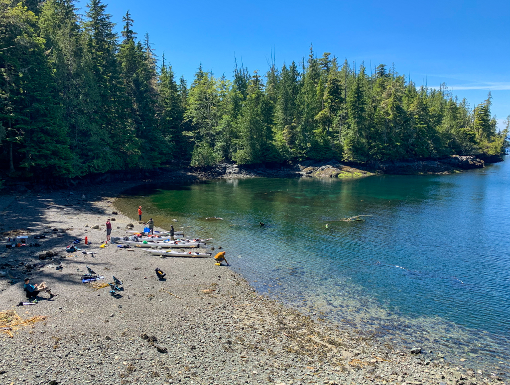 A group of kayakers relax on the beach in the Johnstone Strait