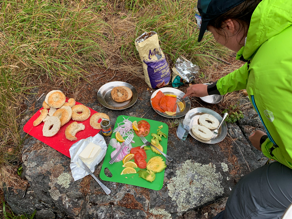 A kayaker makes a bagel sandwich on a guided kayak tour in the Johnstone Strait