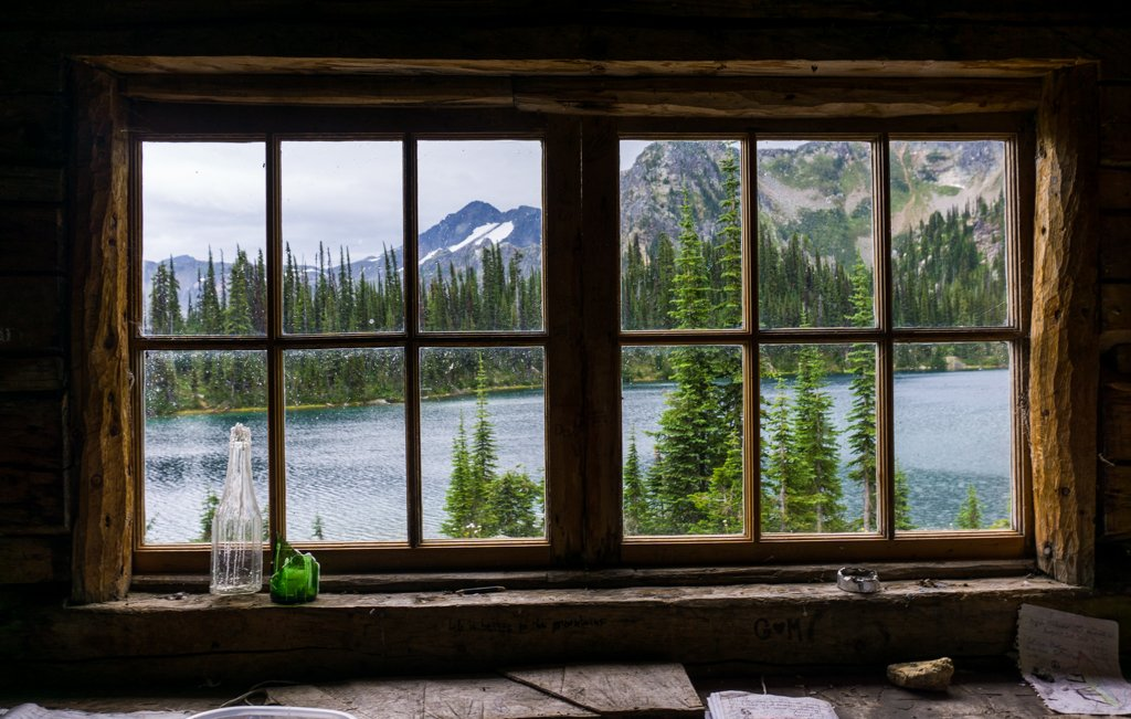 View of Eva Lake in Mount Revelstoke National Park through the window of an old log cabin