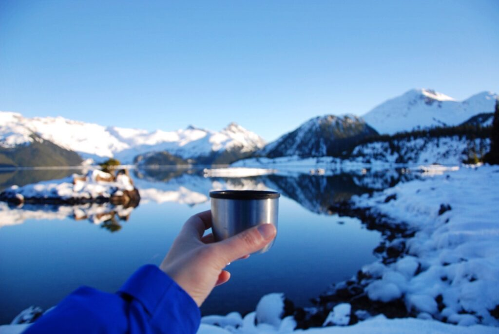 A snowshoer holds a cup of hot chocolate from a thermos in front of a snowy lake