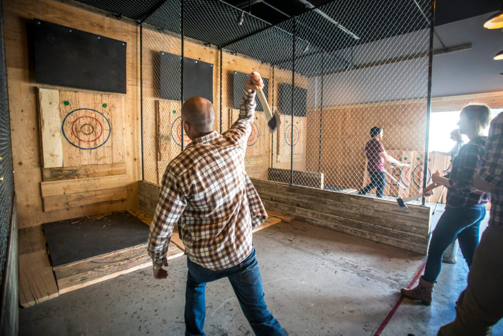 A man throwing an axe at a target at Forged Axe Throwing in Whistler