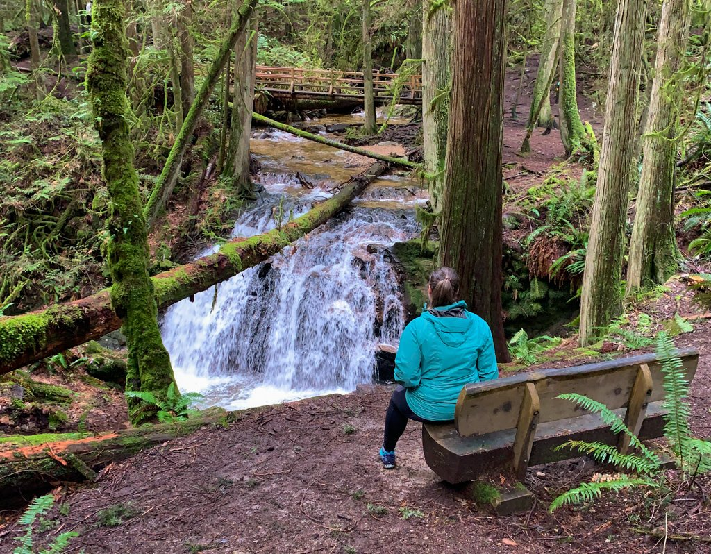 A woman sits on a bench and looks at a waterfall in Cliff Gilker Park on the Sunshine Coast, BC