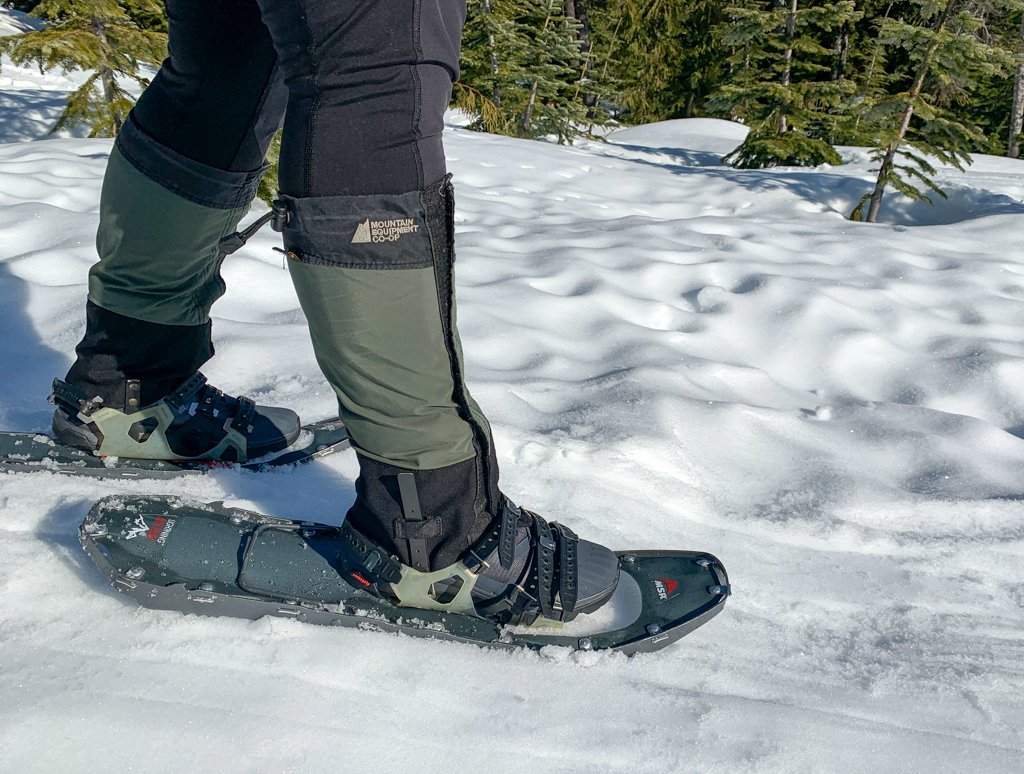 A hiker wears gaiters and snowshoes