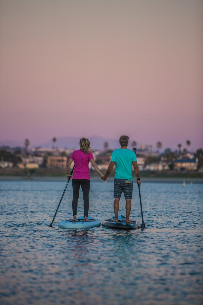 A couple holds hands as they paddleboard at sunset. One of the best Valentine's gifts for hikers and campers - vouchers for paddleboard lessons.