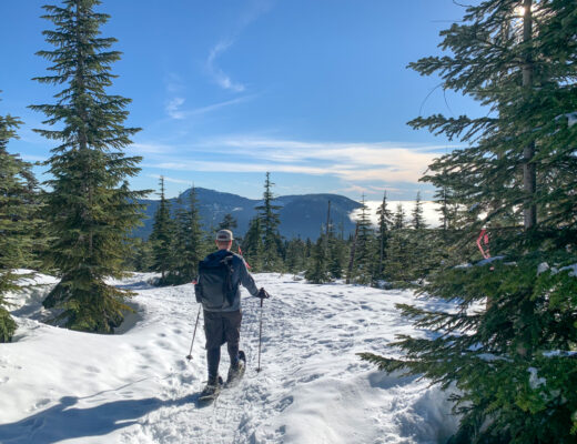A man snowshoeing towards an opening in the trees with a view of the ocean at Dakota Ridge on the Sunshine Coast, BC