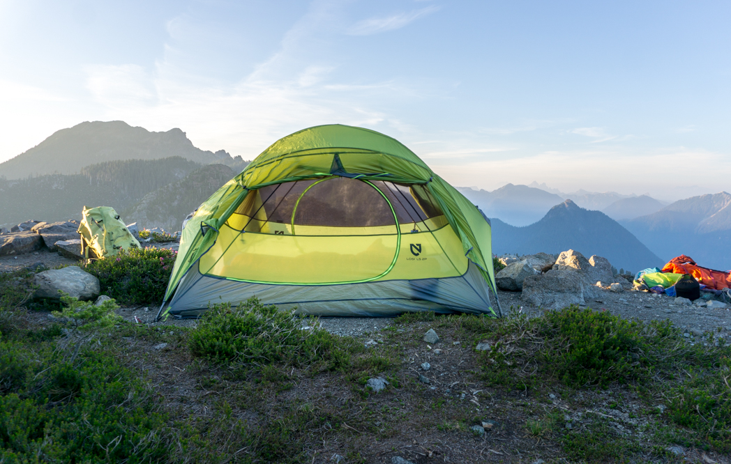 A tent pitched on top of amountain with more mountains in the background - just one of the trips in the book Backpacking in British Columbia