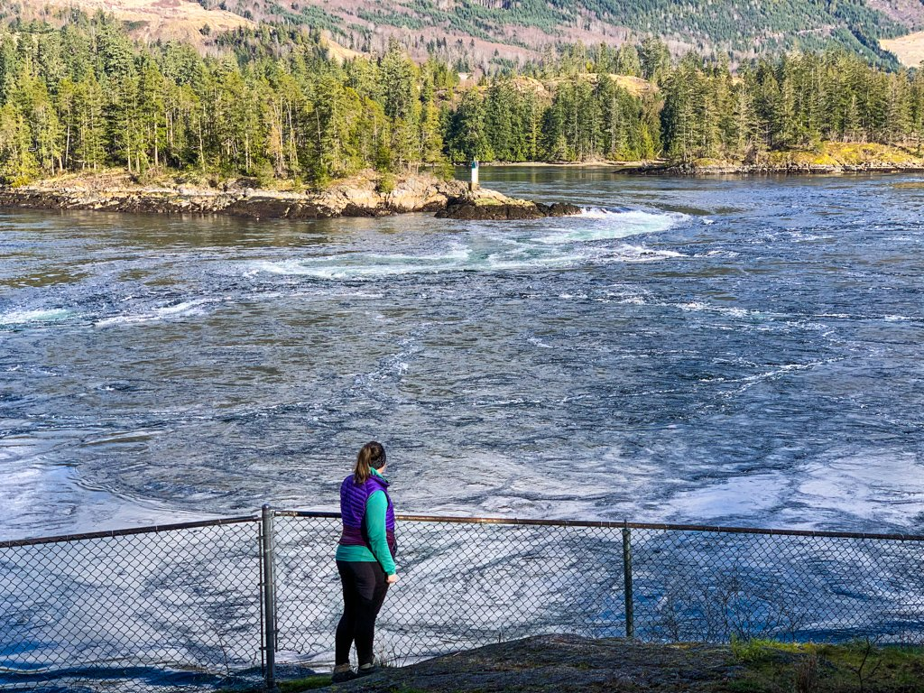 A woman watches the rapids at Skookumchuck Narrows on the Sunshine Coast, BC