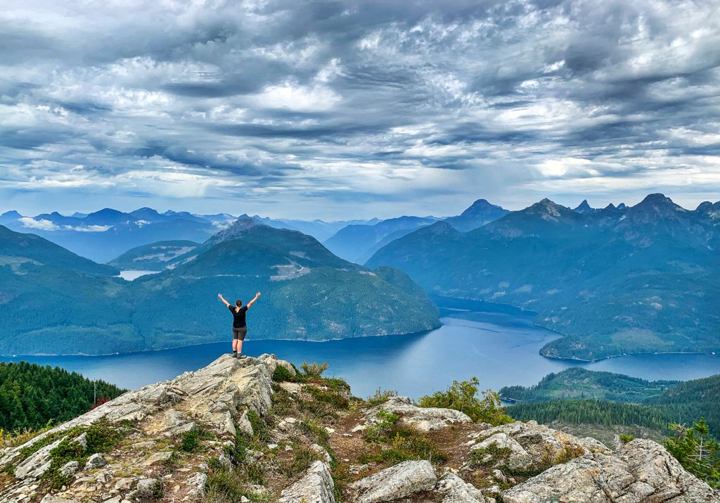 A woman standing at the peak of Tin Hat Mountain on the Sunshine Coast