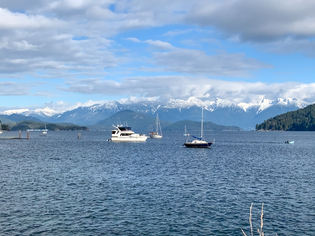 Boats in Gibsons, BC with a view of the Howe Sound Mountains behind