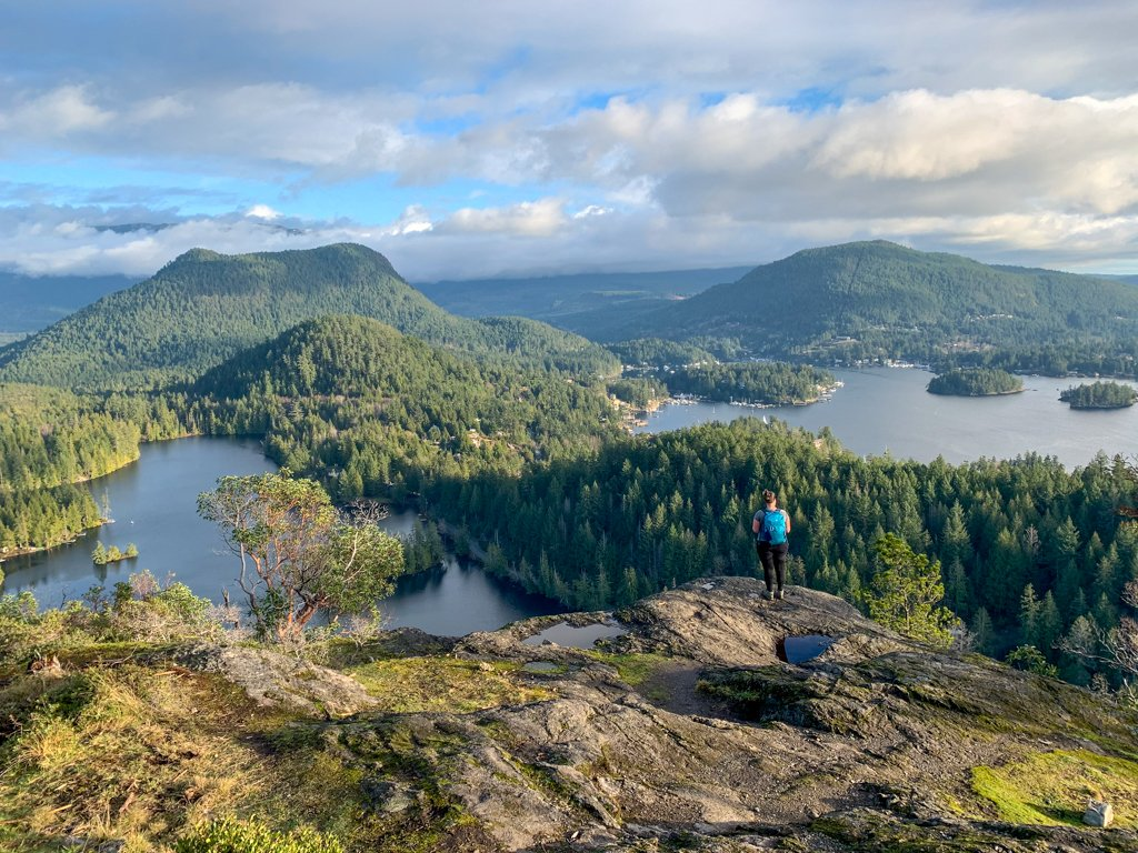 A woman stands on a rocky outcropping on Pender Hill - one of the best hikes on the Sunshine Coast, BC