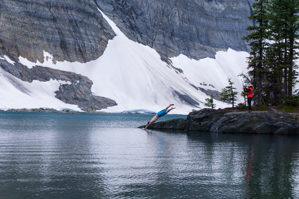 A man dives into Floe Lake on the Rockwall Trail