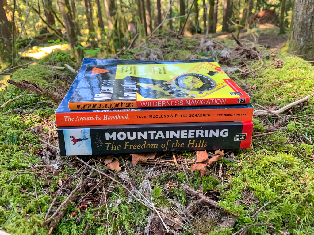 Three outdoor skills and wilderness education books for hikers stacked on moss