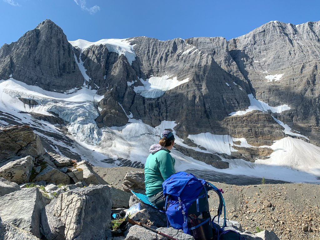 A woman sitting down next to a backpack and looking at a glacier on the Rockwall Trail