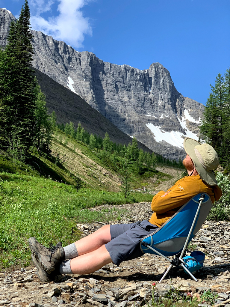 A man sits in a chair at Tumbling Pass on the Rockwall Trail