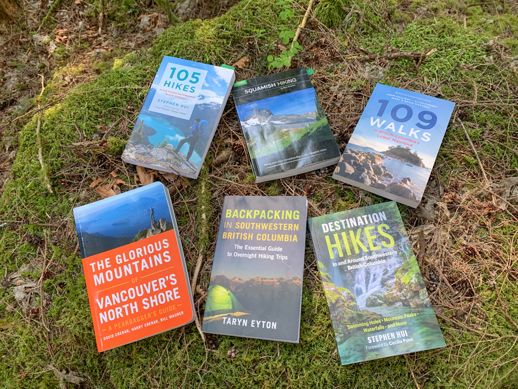Six Vancouver hiking guidebooks spread across moss