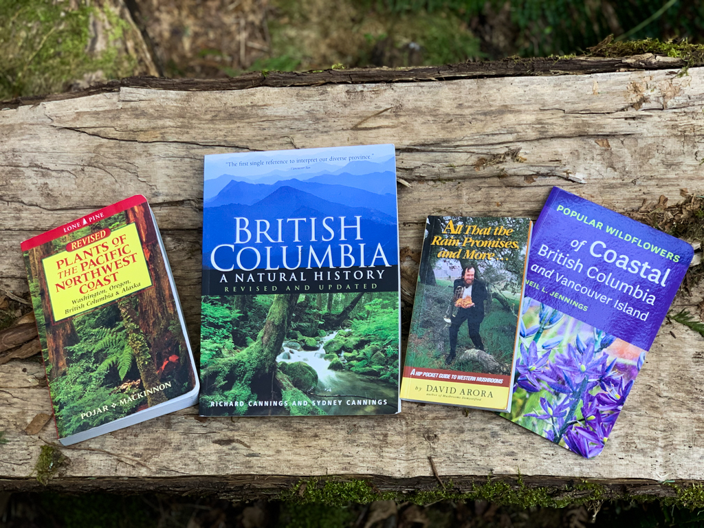 Four British Columbia and Vancouver natural history books spread across a log