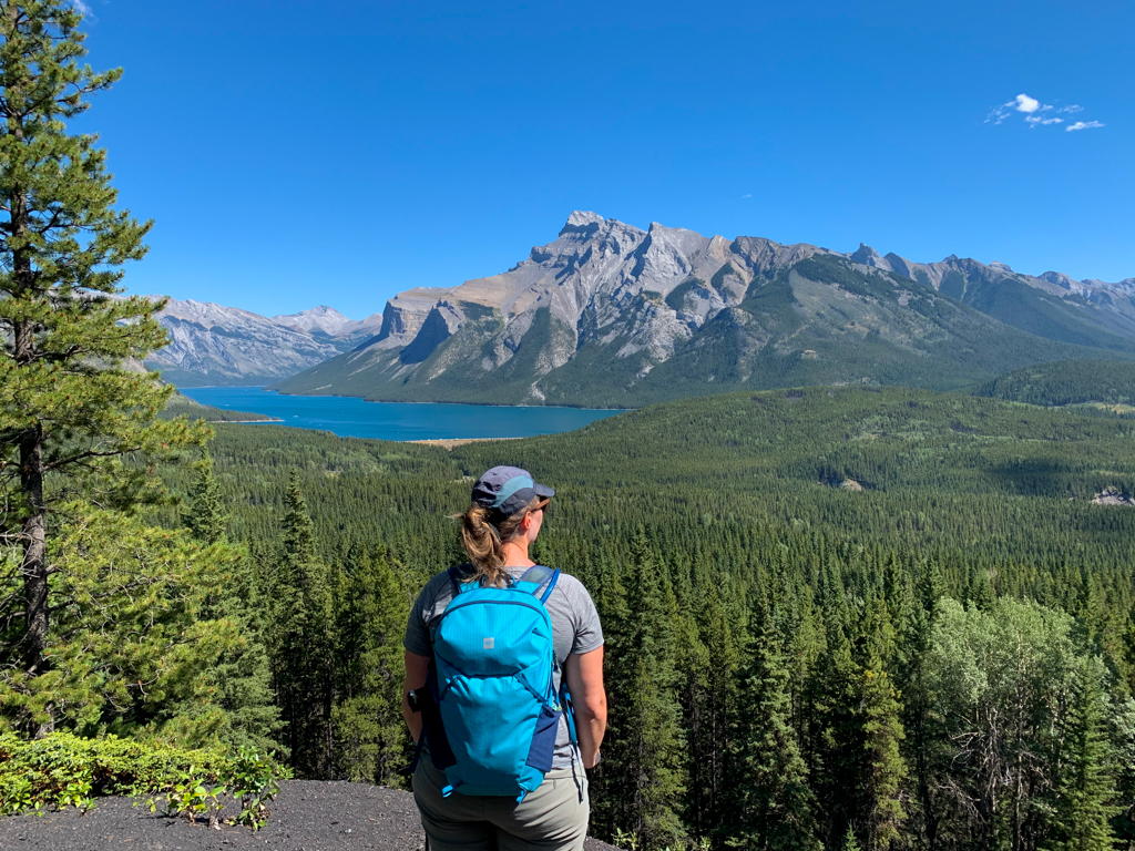 A woman stands at a viewpoint about Lake Minnewanka in Banff National Park