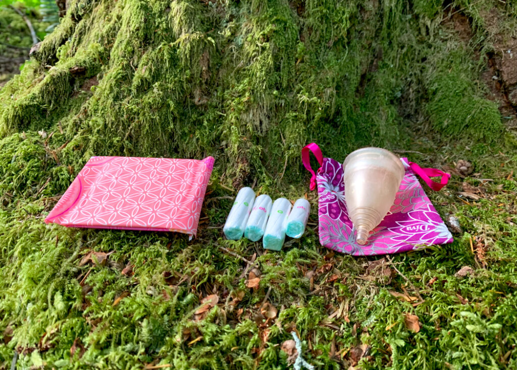 Pads, tampons and a menstrual cup in the forest. Learn how to go hiking with your period.